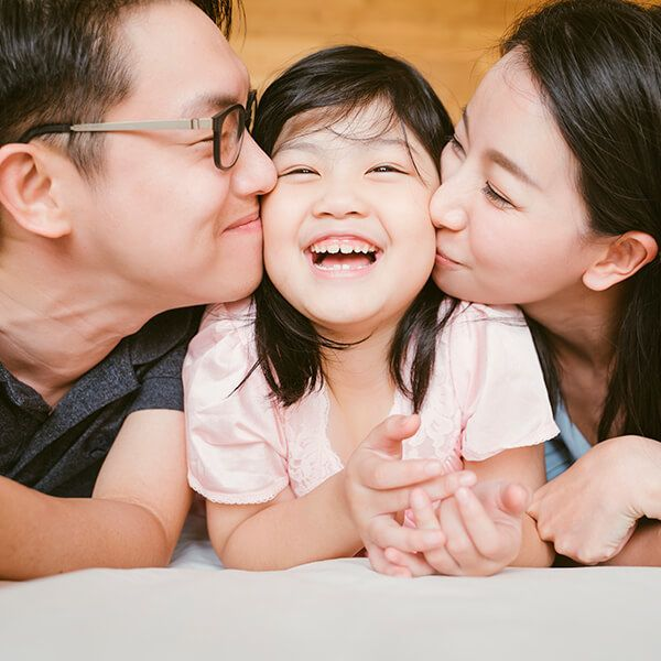 Two parents kissing their child after visiting the dentist