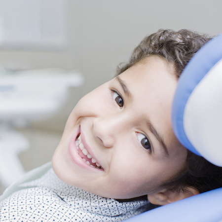 Young boy in dental chair getting ready for sealants on his teeth