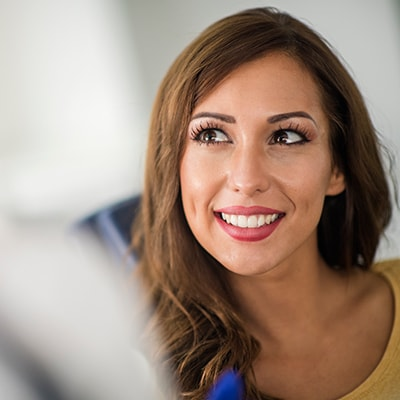 A woman smiling after receiving an oral cancer screening